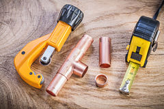 Fita métrica de cobre dos conectores do cortador de tubulação da água na placa de madeira p imagens de stock royalty free