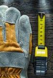 Fita métrica dos pares de luvas da segurança na placa de madeira Imagens de Stock Royalty Free