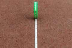 Fita métrica verde que encontra-se em um estádio vermelho da pista de atletismo Imagens de Stock Royalty Free