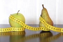 Fita, maçã e pera de medição fotografia de stock royalty free