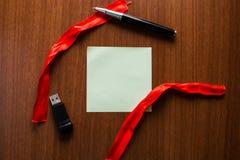 Fita vazia quadrada de encontro das listras da nota dois da tabela de madeira da memória de USB acima abaixo da pena Folha deskto fotografia de stock