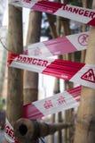Fita vermelha do perigo envolvida em torno do bambu imagem de stock