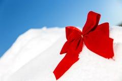 Fita vermelha grande na neve, céu azul no fundo Imagem de Stock