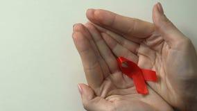 Fita vermelha nas mãos fêmeas, cuidado de pacientes de VIH, prevenção da epidemia de SIDA vídeos de arquivo
