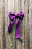 Fita violeta do cetim no fundo de madeira Fotografia de Stock