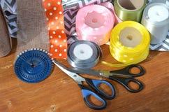 Fitas, tesouras e pinos da cor ajustados na prancha de madeira foto de stock