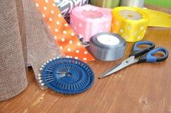 Fitas, tesouras e pinos da cor ajustados na prancha de madeira fotografia de stock