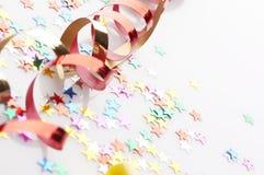 Fitas vermelhas e douradas e confetti pequeno coloridos Fotos de Stock Royalty Free