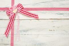 Fitas vermelhas e uma curva em um fundo de madeira Imagens de Stock Royalty Free