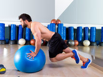 Fitball abdominal push ups Swiss ball. Man one single leg pushup at fitness gym Royalty Free Stock Images