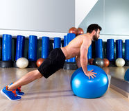 Fitball abdominal push ups Swiss ball man. Pushup at fitness gym Royalty Free Stock Photography