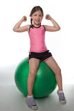 Fitball Girl. A little girl flexes her muscles while sitting on a fitball Stock Images