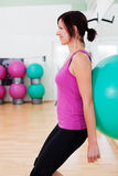 Fitball squat exercise. Smiling young woman doing a fitball squat exercise stock images