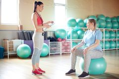 Fitball training instruction. Young fitness instructor consulting oversized female before fitball training in gym stock photos