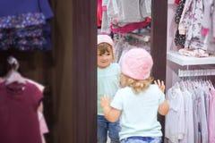 fiting在衣裳的逗人喜爱的小女孩在商店 免版税图库摄影