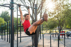 Fitnes man hanging on wall bars performing legs raises. Core cross training working out abs muscles.  stock image