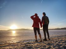 Fitnes-Paarmann und -frau Winterlandschaft mit Sonne lizenzfreie stockfotos
