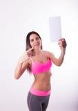 Fitnes castana in una tuta sportiva che tiene bordo bianco vuoto Immagine Stock