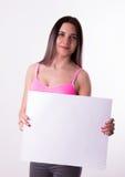 Fitnes castana in una tuta sportiva che tiene bordo bianco vuoto Fotografia Stock Libera da Diritti