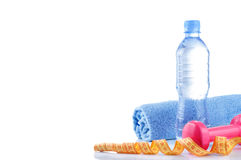 Fitnes symbols - red dumbbells, a bottle of water and a towel. The concept of a healthy lifestyle Royalty Free Stock Photos