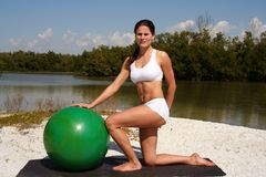 Fitness. Woman on beach using a fitness ball Royalty Free Stock Image