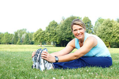 Fitness. Mature woman working out in park stock photos