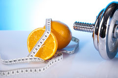 Fitness. Oranges and dumbell with measure tape Royalty Free Stock Image