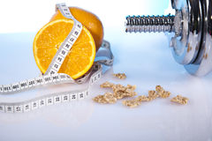 Fitness. Oranges and dumbell with measure tape Stock Photos