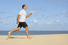 Fitness. Healthy sportive man jogging at the beach Stock Photography