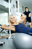 Fitness. Happy cutie athletic girl ,  execute exercise on muscles belly  and smile, in  sport-hall Stock Image