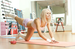 Fitness. Happy cutie athletic girl ,  execute exercise  and smile, in  sport-hall Stock Image