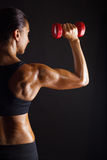 Fitness. Woman with barbells on dark background Stock Photos