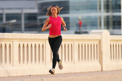Fitness. A beautiful athletic woman running in an urban environment Royalty Free Stock Photos