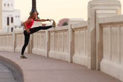 Fitness. A beautiful athletic woman stretches before running in an urban environment Royalty Free Stock Images