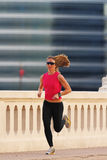 Fitness. A beautiful athletic woman running in an urban environment Stock Image