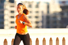 Fitness. A beautiful athletic woman running in an urban environment royalty free stock photography