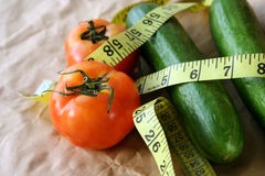 Fitness. Tomato & cucumber with measuring tape around in white background Royalty Free Stock Photo