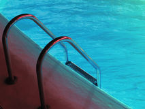 Fitness. Swimming pool ladder and clean blue water royalty free stock images