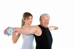 Fitness. Senior man and young woman exercising in gym. Copy space Stock Photos