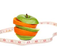 Fitness. Concept-  slices of apple and orange and tape measure Royalty Free Stock Photo