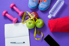 Fitness accessories with opened book, apples, mobile phone and measuring tape Stock Image