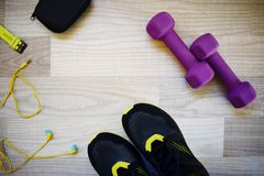 Fitness accessories: dumbbells, sneakers, earphones royalty free stock photo