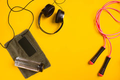 Fitness accessories on a yellow background. skipping rope, bottle of water, towel and headphones. stock photo