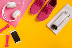Fitness accessories on a yellow background. Sneakers, bottle of water, earphones and dumbbells. Still life Stock Images