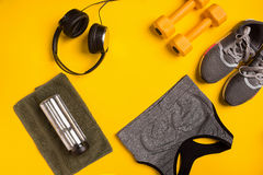 Fitness accessories on a yellow background. Sneakers, bottle of water, smart, towel and sport top. Stock Photos