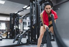 Fitness active brunette sportswoman working out in functional training gym doing crossfit exercise with battle ropes with red royalty free stock photography