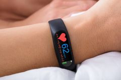 Fitness Activity Tracker With Heartbeat Rate On Woman`s Hand. Close-up Of Fitness Activity Tracker With Heartbeat Rate On Woman`s Hand Over Bed royalty free stock photos