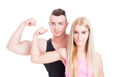 Fitness and aerobic trainers or couple. Flexing biceps with confidence on white studio background Royalty Free Stock Photo
