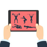 Fitness app for tablet. Hands holding tablet. Bodybuilding app. How to do gym exercises like lifting weights, pull ups, crunches, squats and plank Stock Photo