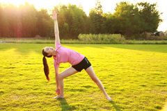 Fitness Asian Chinese woman do yoga. Asian Chinese woman in red sports suit,at outdoor, on grass, do yoga, inner peace, healthy life, do exercise, natural Stock Photography